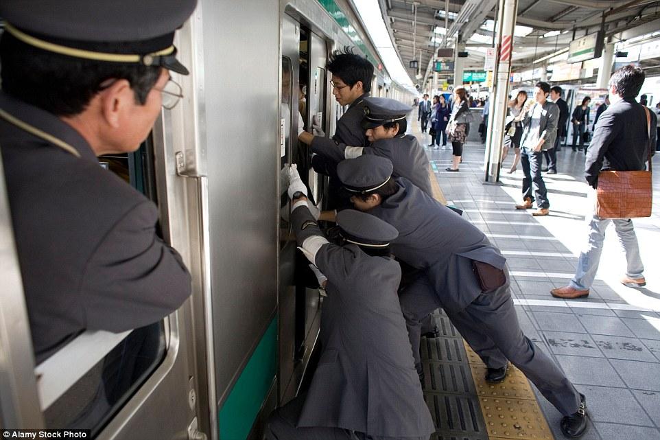 Nhân viên nhồi nhét các hành khách lên tàu cho kịp giờ tàu xuất phát